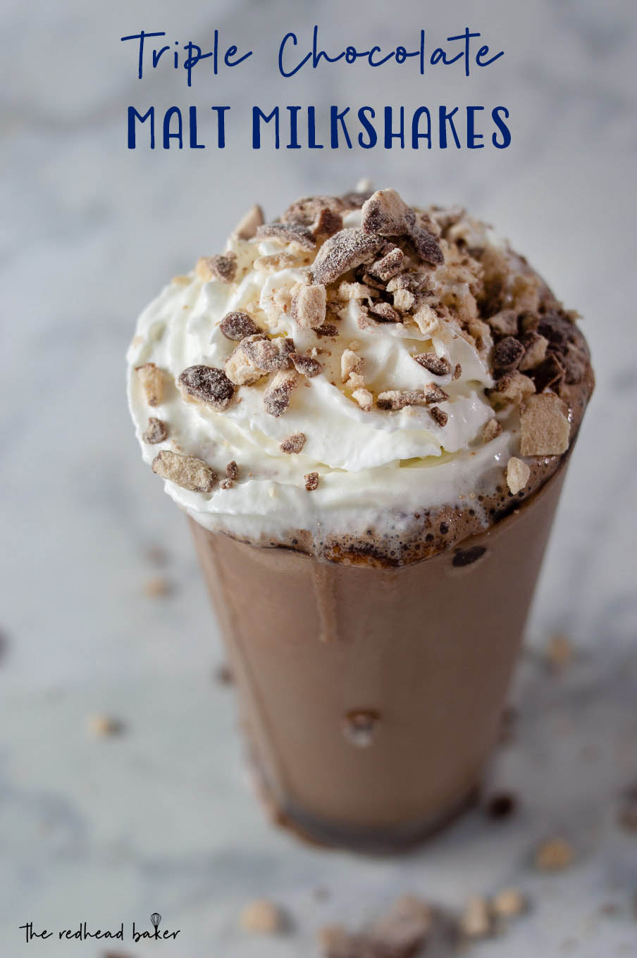 A triple chocolate malt milkshake garnished with whipped cream and crushed malted milk candies