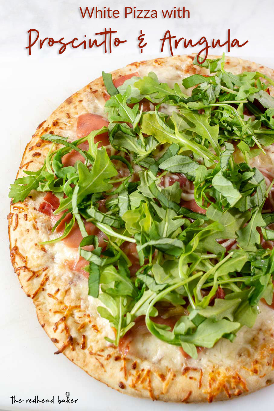 An overhead photo of a whole white pizza with prosciutto and arugula
