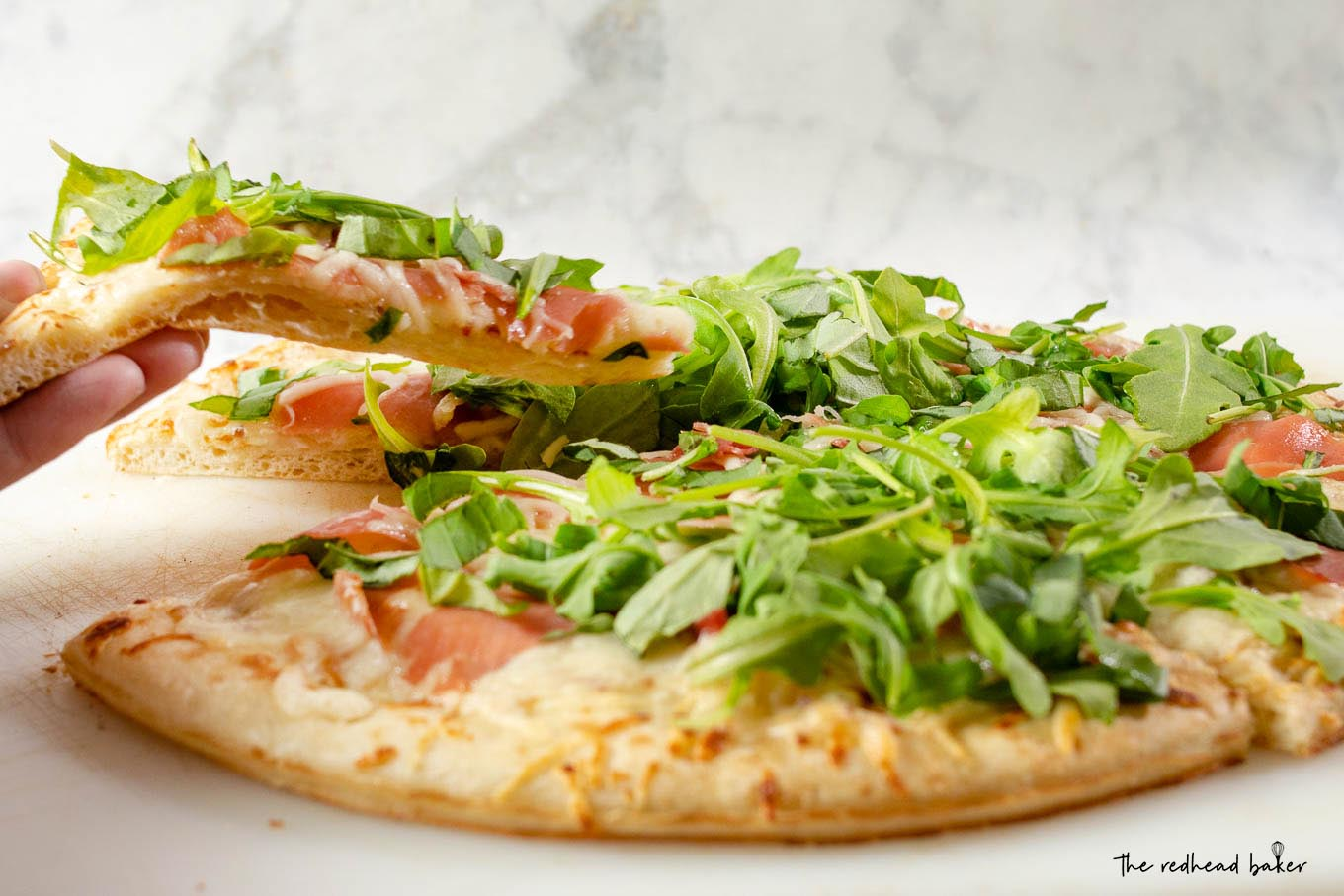 A slice of white pizza with prosciutto and arugula being lifted from the rest of the pizza