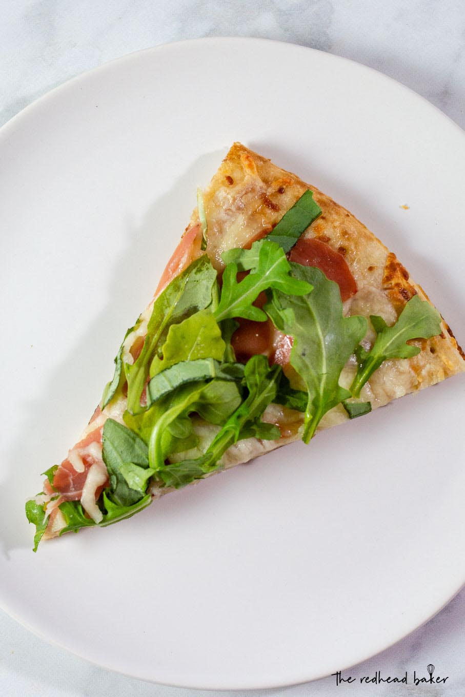 An overhead photo of a slice of white pizza with prosciutto and arugula