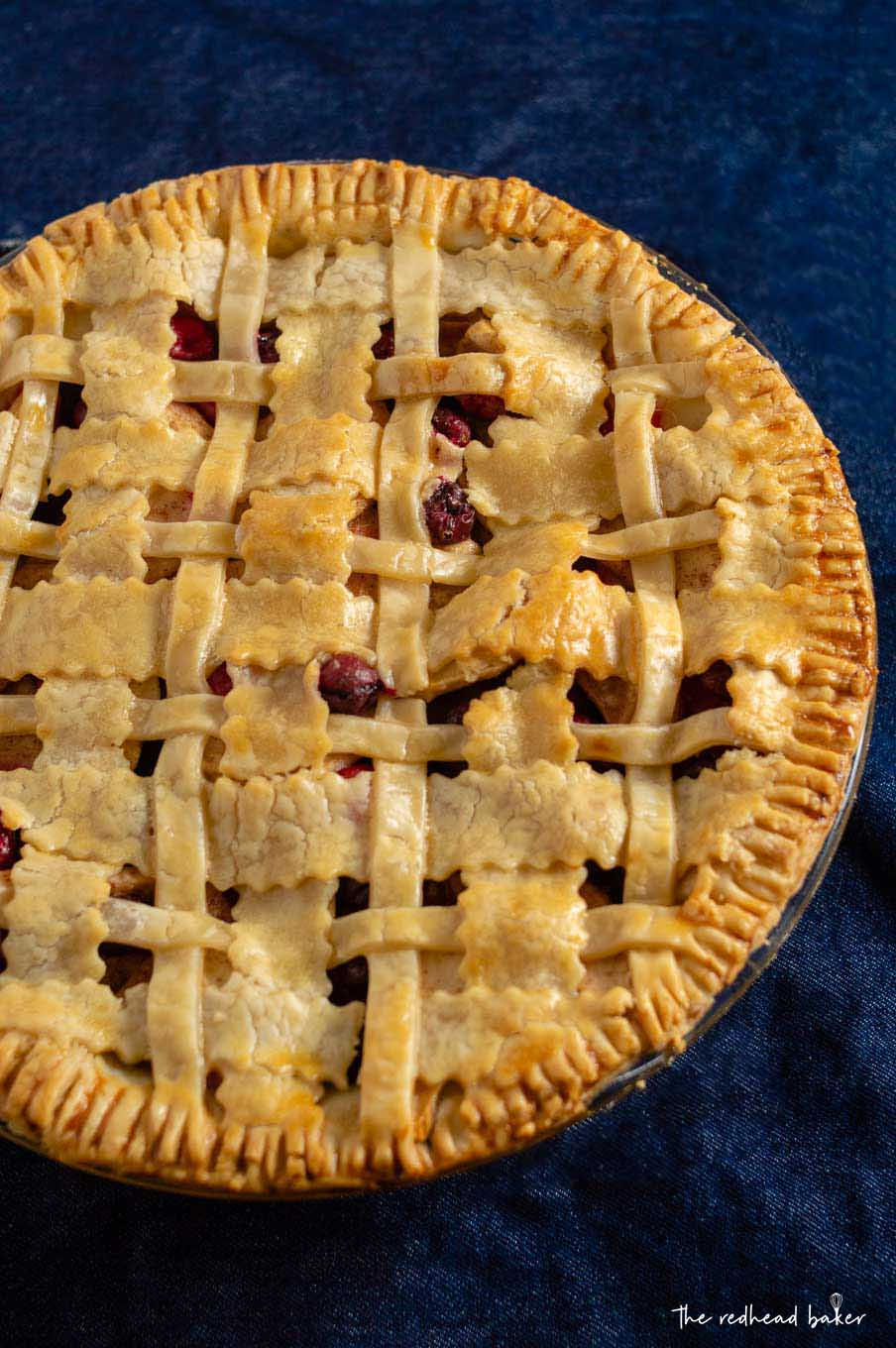 An overhead shot of a whole cranberry apple pie