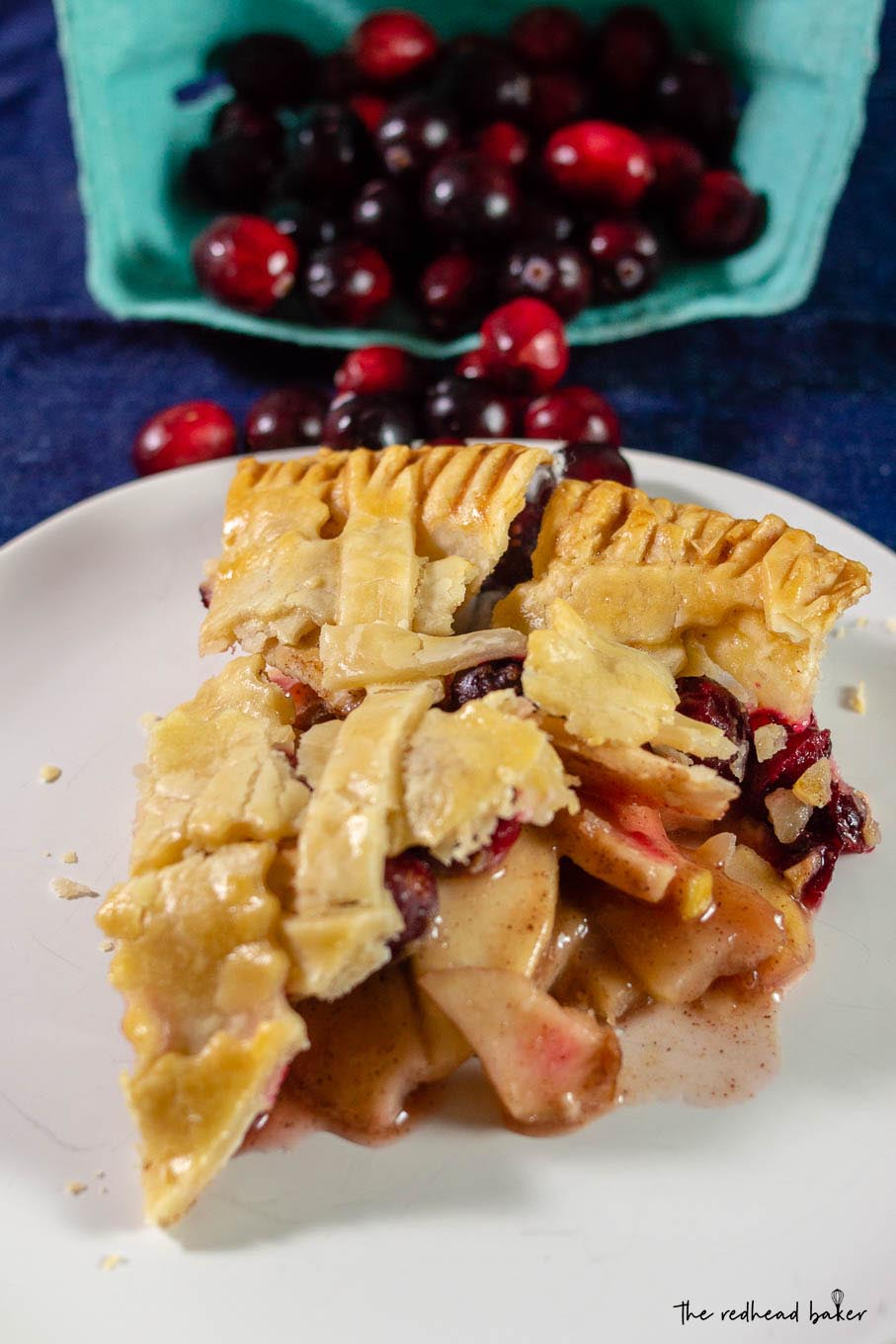 A slice of cranberry apple pie in front of a container of cranberries