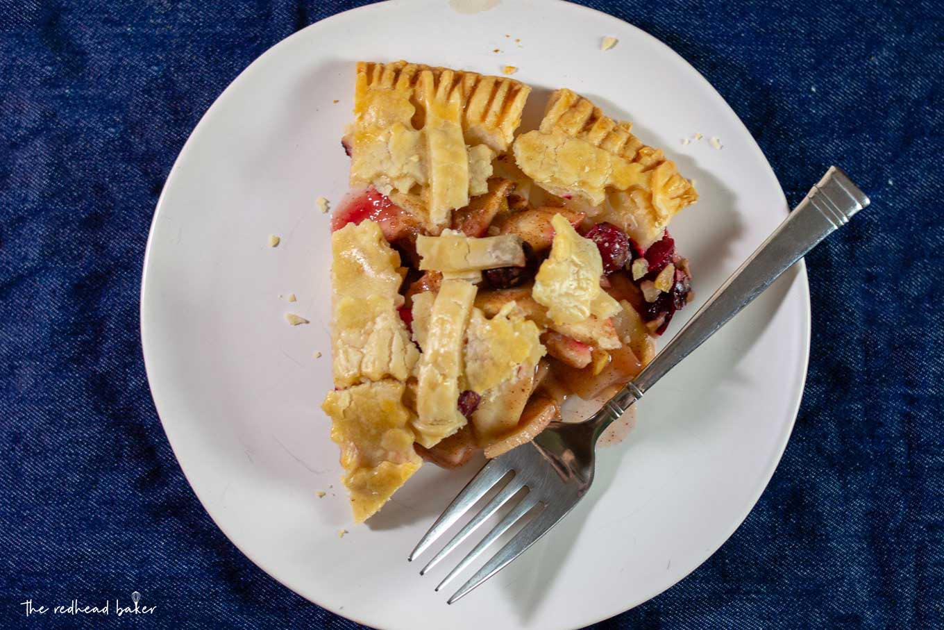 An overhead shot of a slice of cranberry apple pie