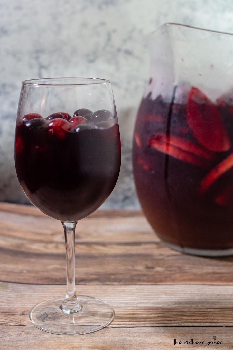 A glass of cranberry apple sangria in front of a pitcher