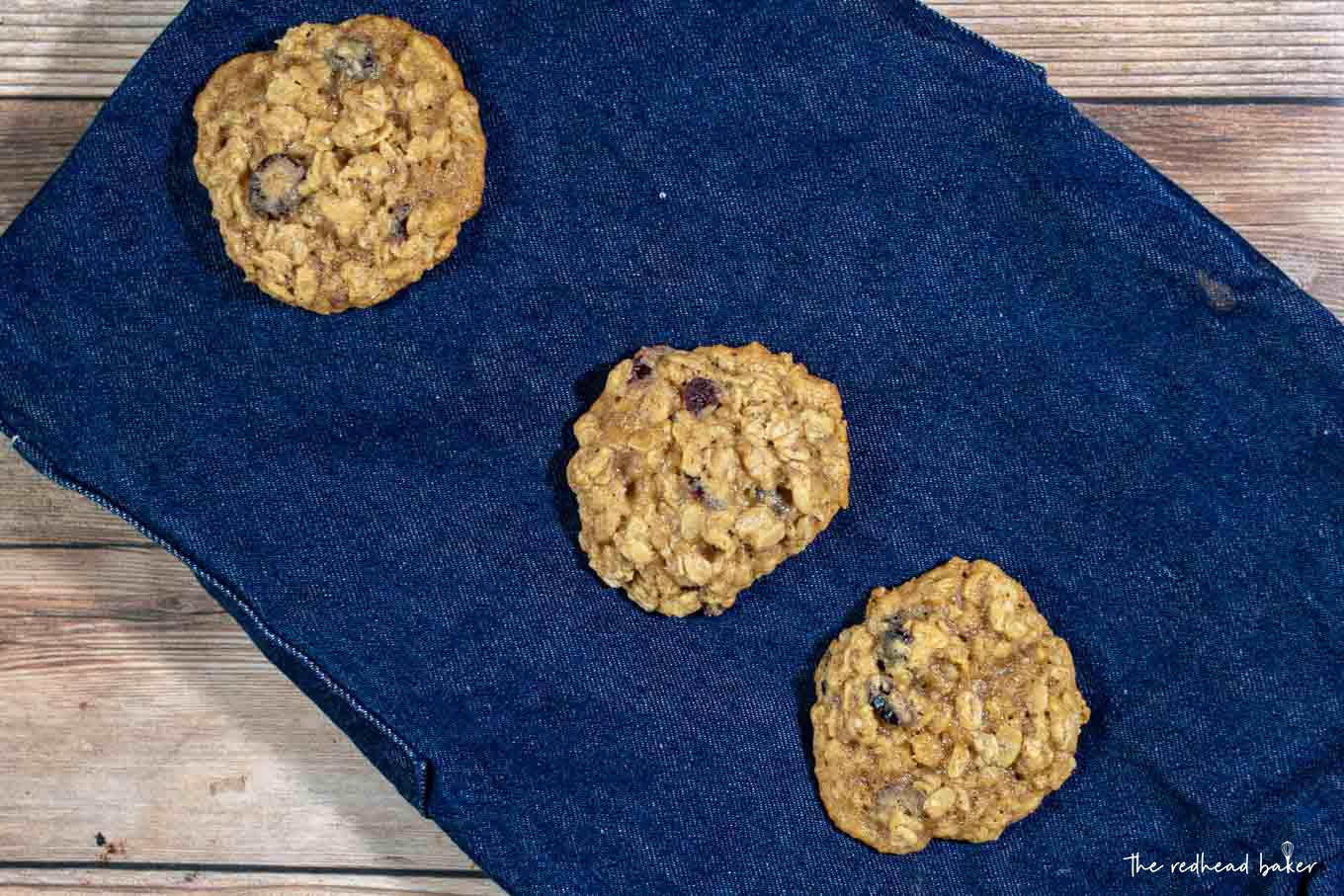 Three cranberry-orange oatmeal cookies on a blue placemat