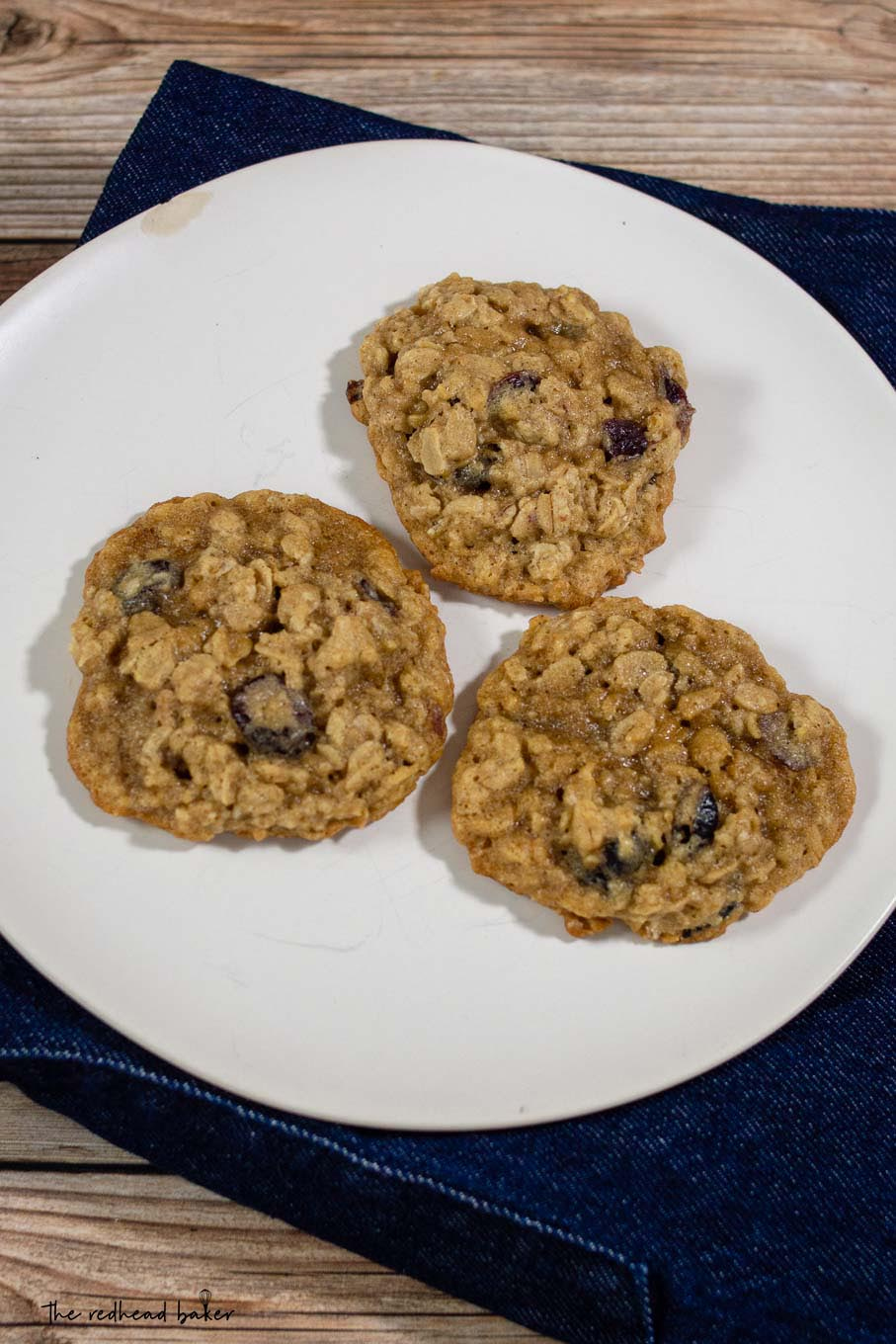 Three cranberry-orange oatmeal cookies on a plate
