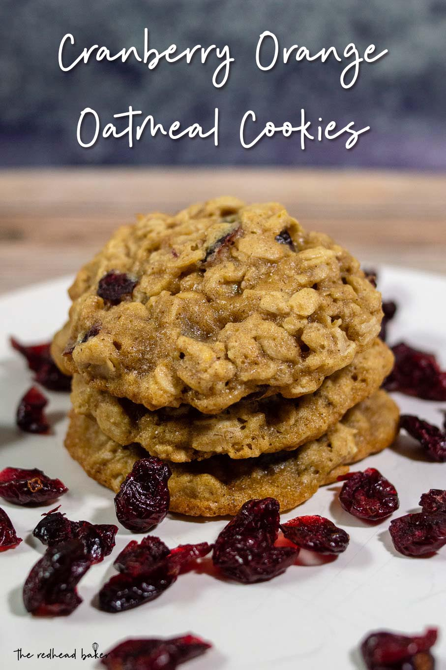 Three cranberry-orange oatmeal cookies in a stack surrounded by dried cranberries