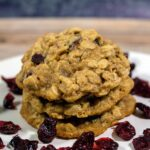 Three cranberry-orange oatmeal cookies in a stack