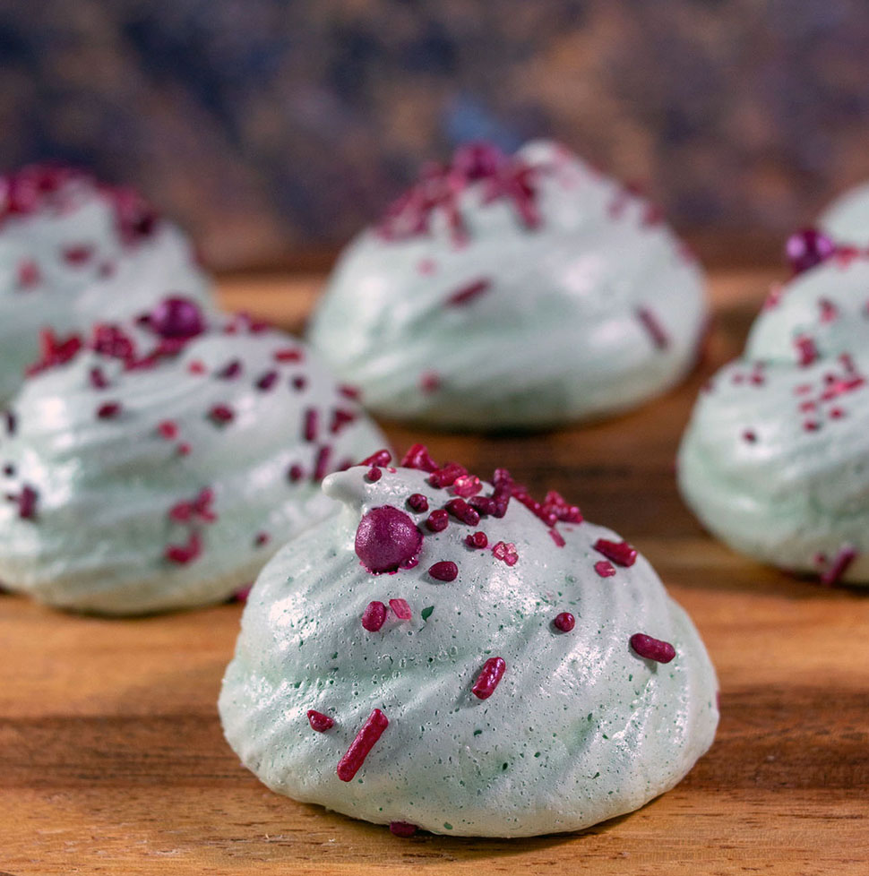 Six meringue cookies on a wooden bardo
