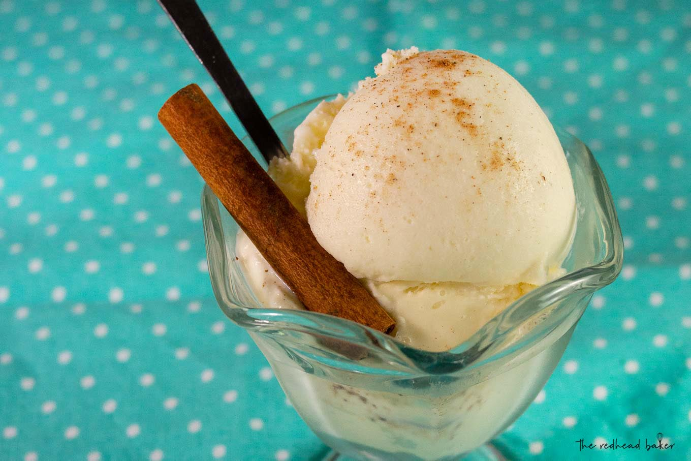 A dish of eggnog gelato with a cinnamon stick and a long ice cream spoon
