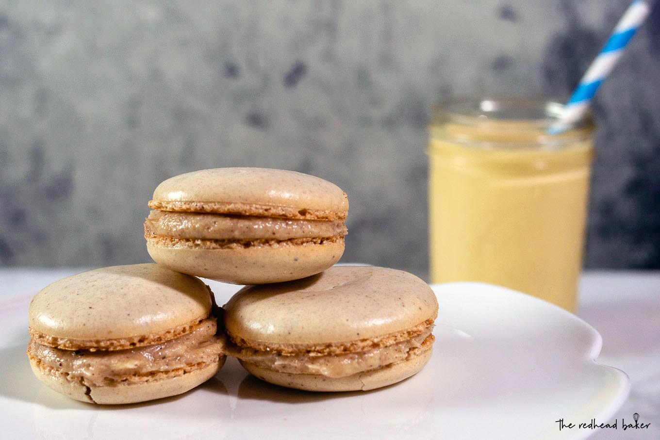 Three eggnog macarons on a cake plate in front of a mason jar of eggnog
