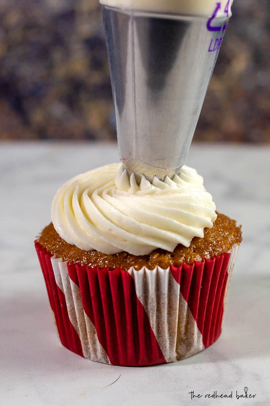 Sweetened cream cheese frosting being piped onto a gingerbread cupcake