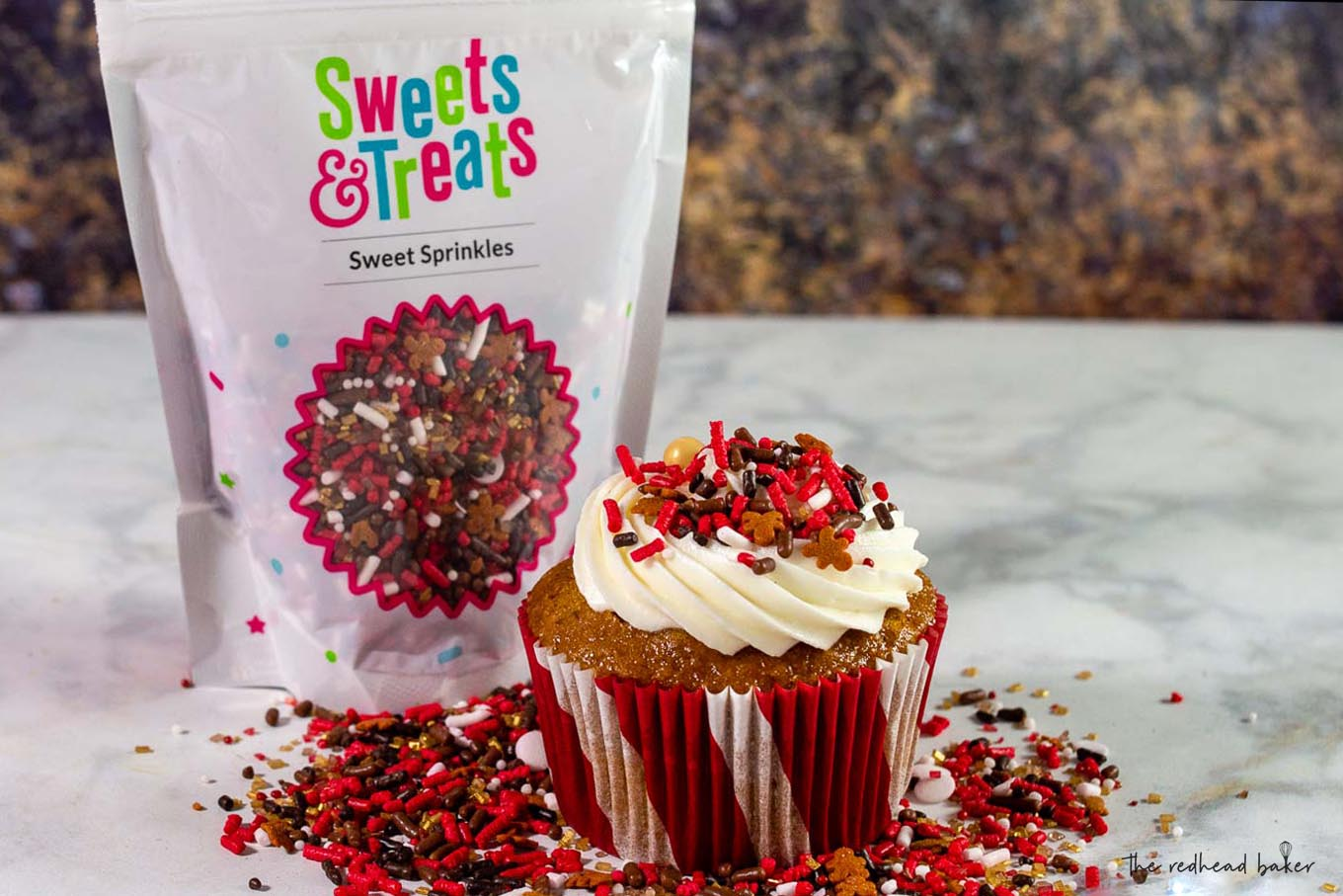 A gingerbread cupcake with cream cheese frosting in front of a bag of Sweets and Treats gingerbread sprinkles