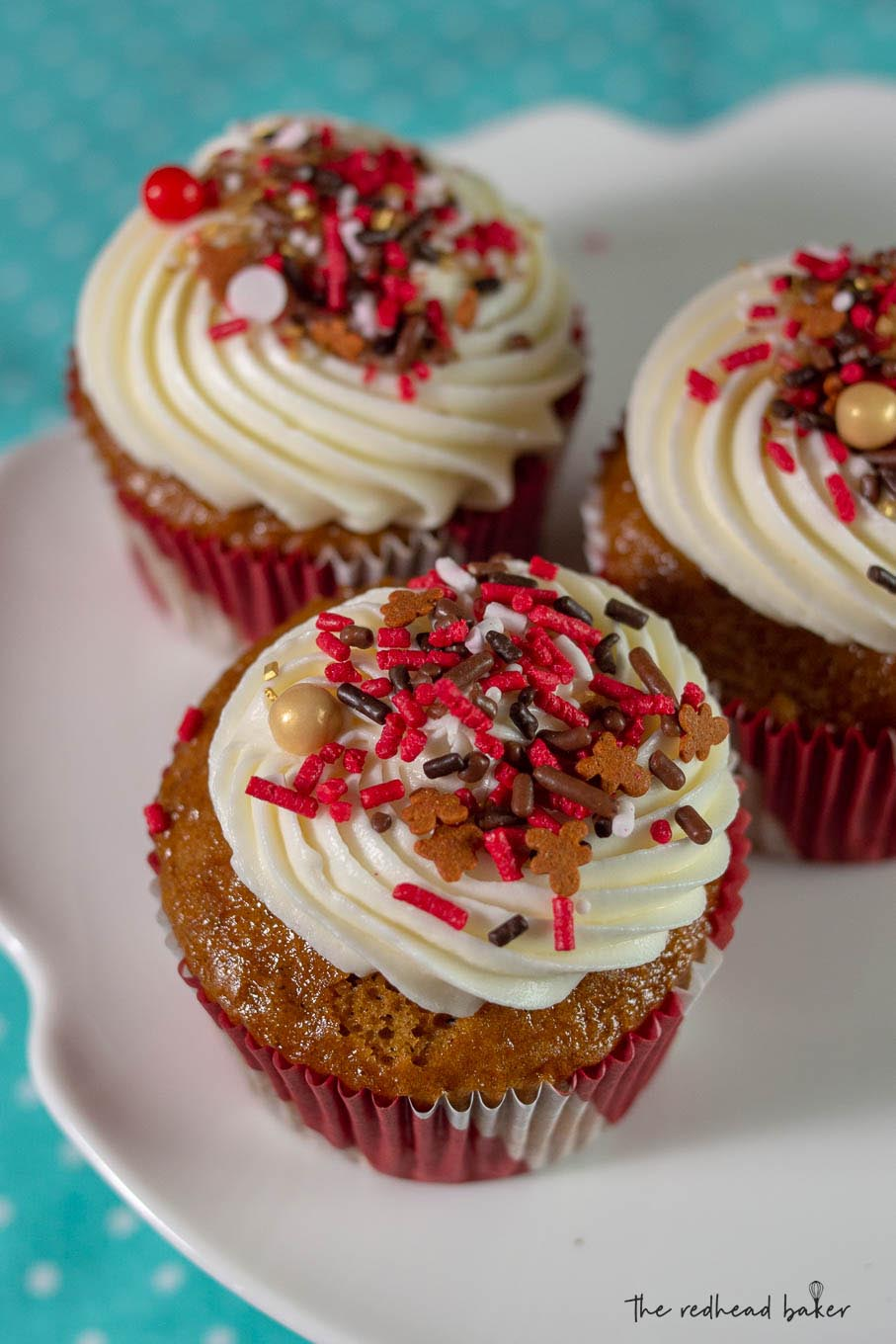 Three gingerbread cupcakes on a white cake stand