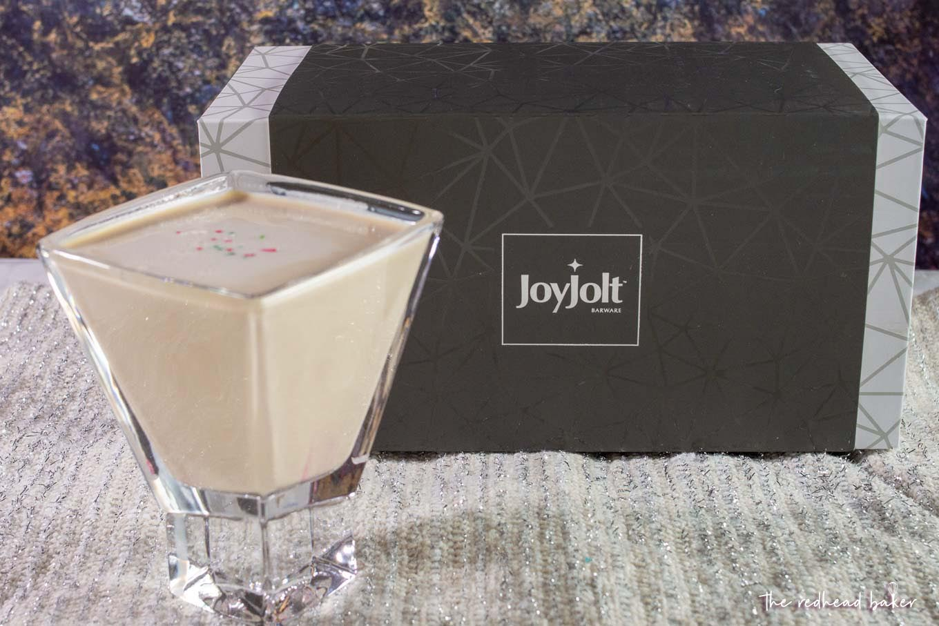 A sugar cookie martini in front of a box of Joy Jolt glassware