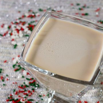 A sugar cookie martini sitting amongst snowflake sprinkles
