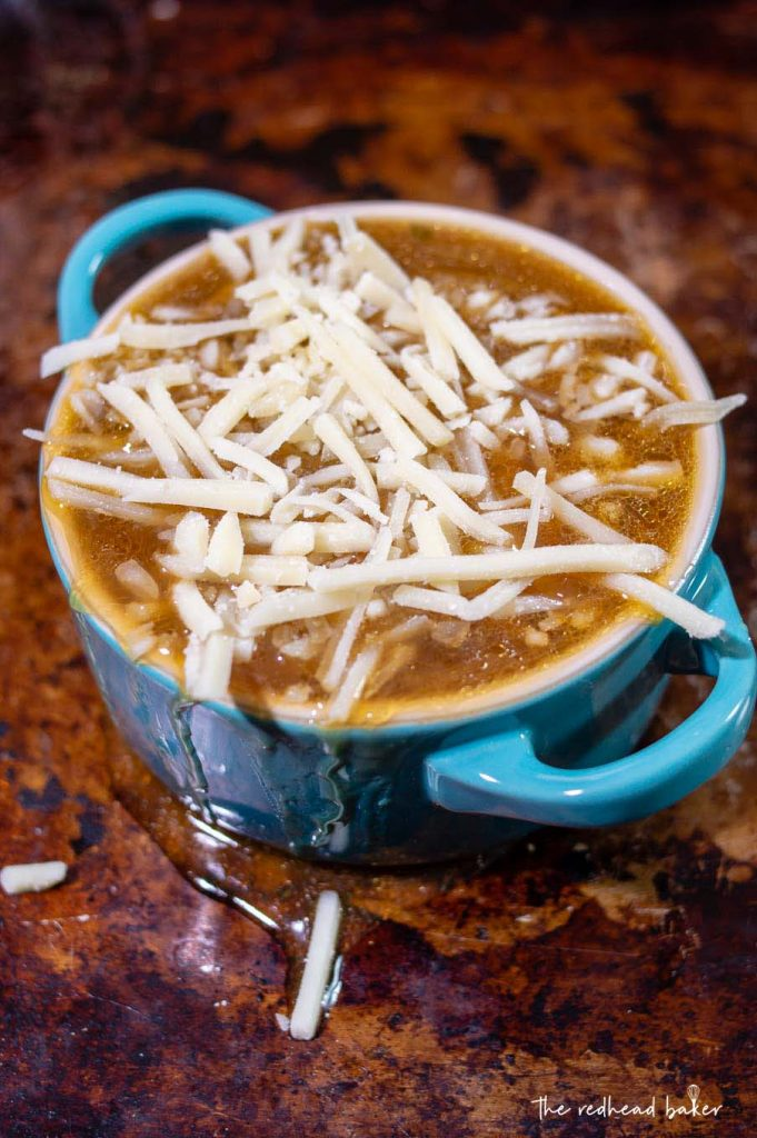 A cocette of French onion soup on a baking sheet with shredded Gruyere cheese on top
