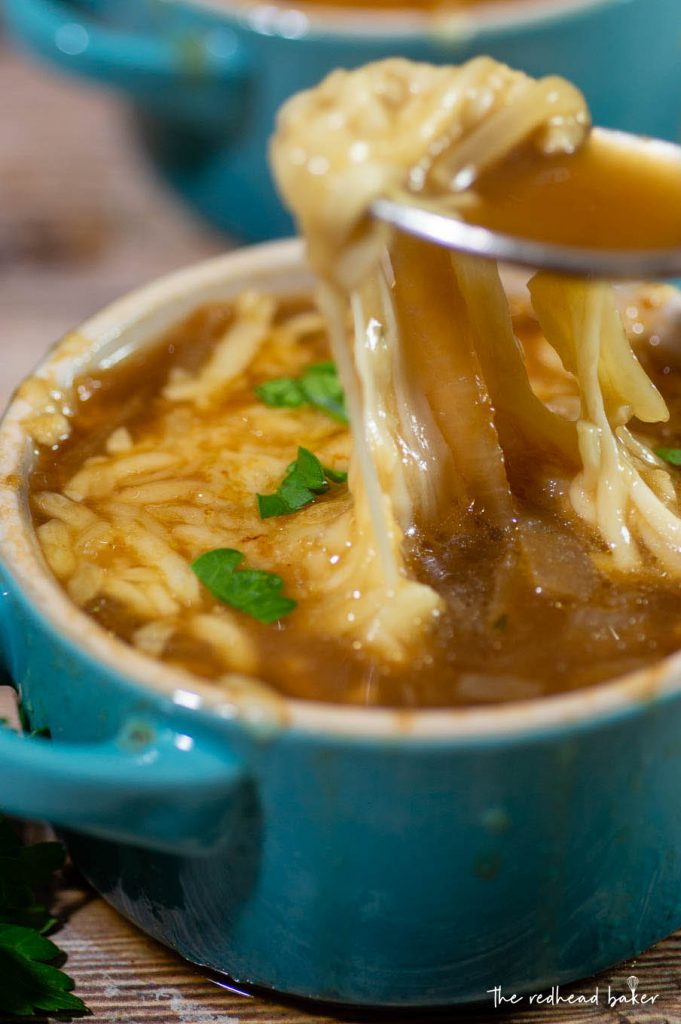 A photo of a spoon lifting the melty cheese up from the cocette of French onion soup