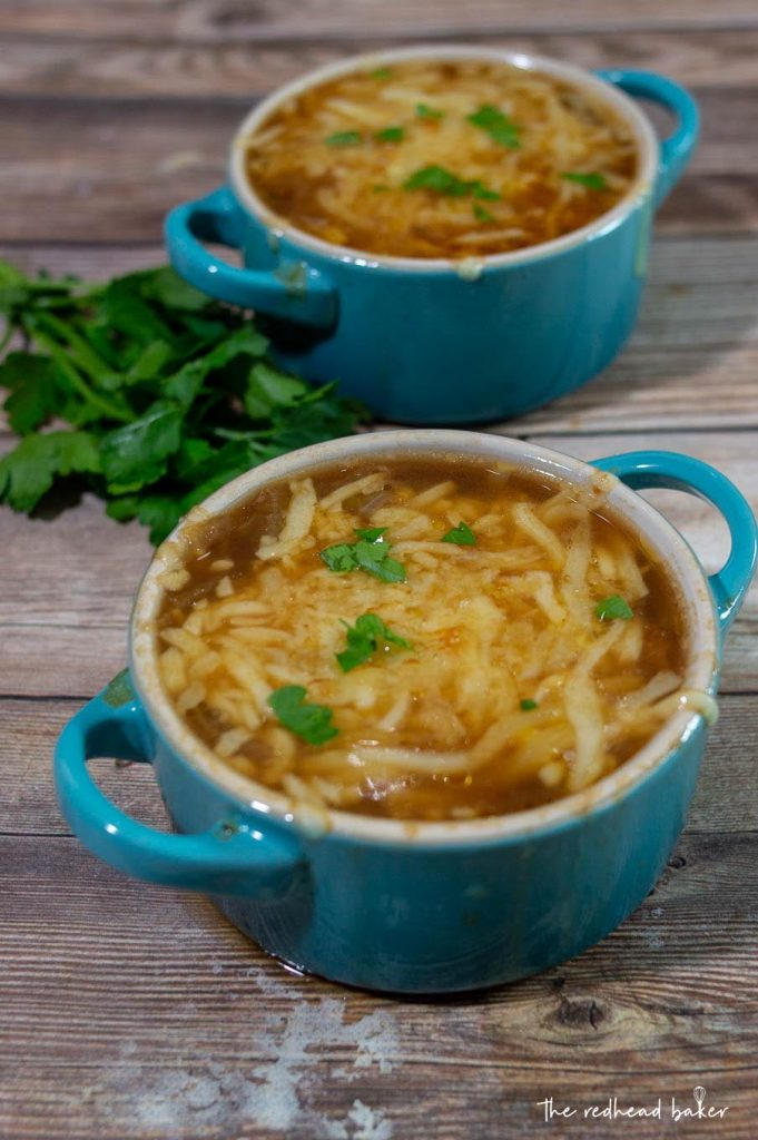 Two cocettes of French onion soup with a bunch of parsley on the side