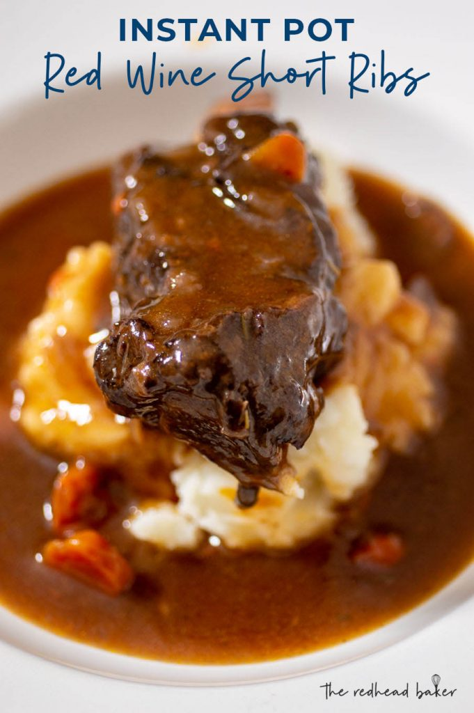 A close up of a bowl of mashed potatoes with a short rib on top surrounded by a pool of gravy