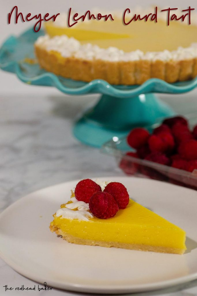 A slice of meyer lemon curd tart on a plate, garnished with whipped cream and raspberries
