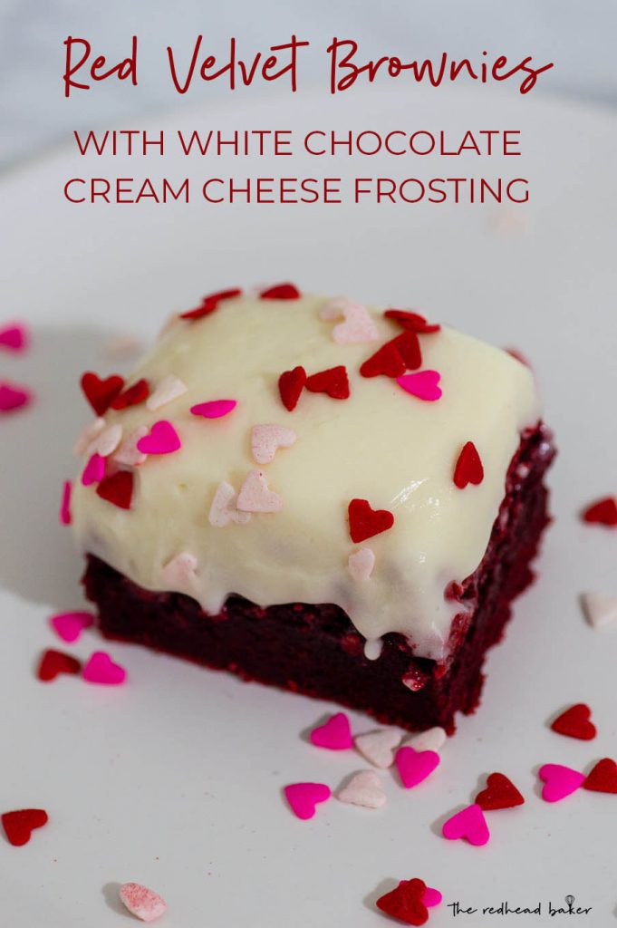 A red velvet brownie on a white plate with heart-shaped sprinkles
