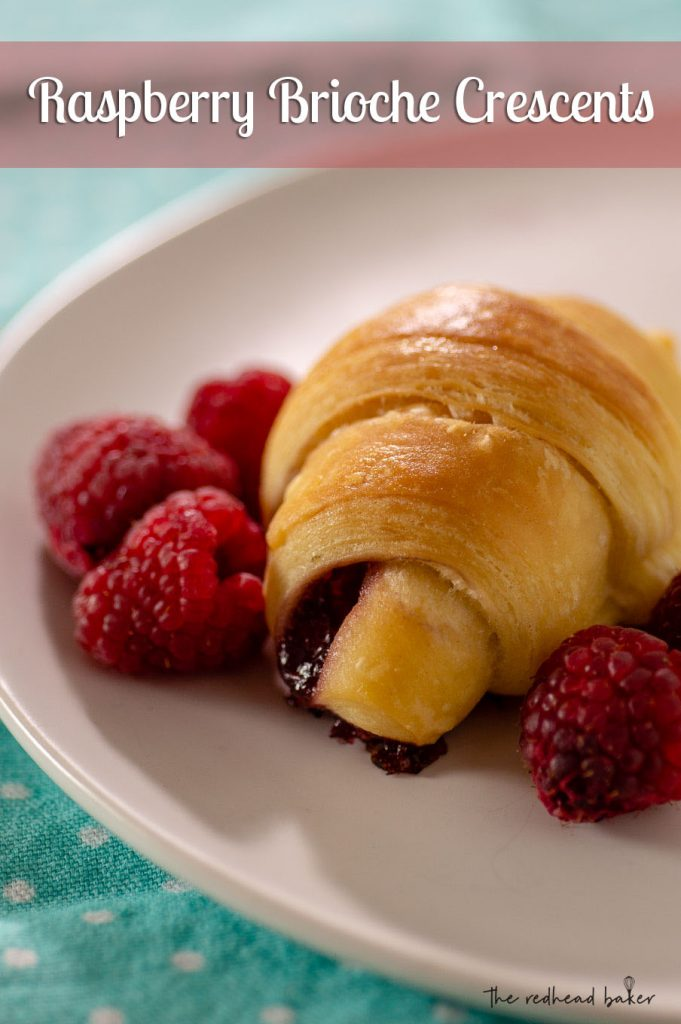 A raspberry brioche crescent on a plate with fresh raspberries