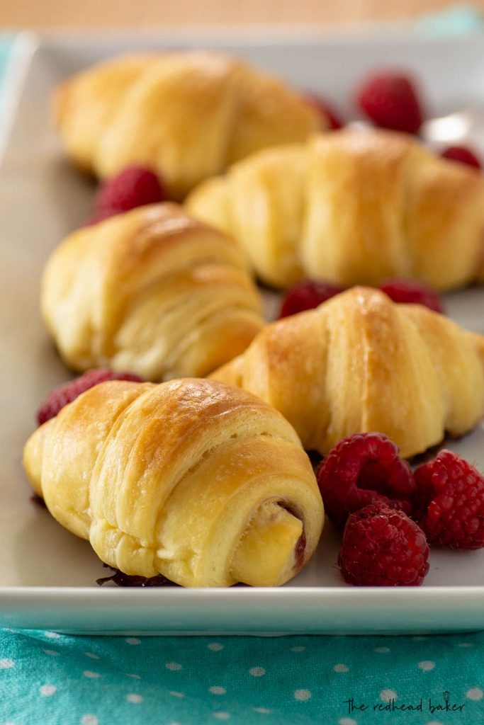 A serving tray of raspberry brioche crescents and fresh raspberries