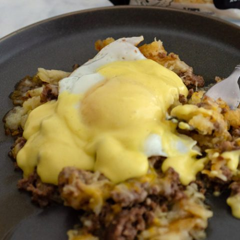 A plate of breakfast poutine topped with a fried egg and Hollandaise