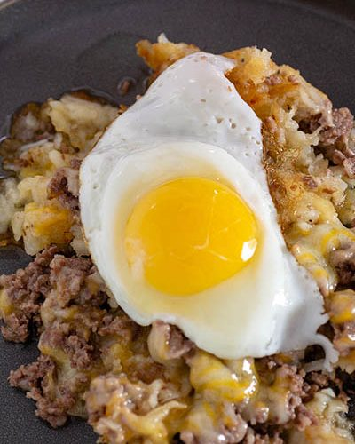 A plate of breakfast poutine topped with a fried egg