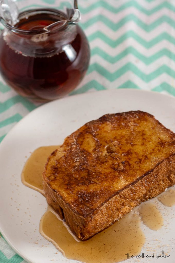 An overhead view of two slices of churro French toast on a white plate in front of a pitcher of syrup