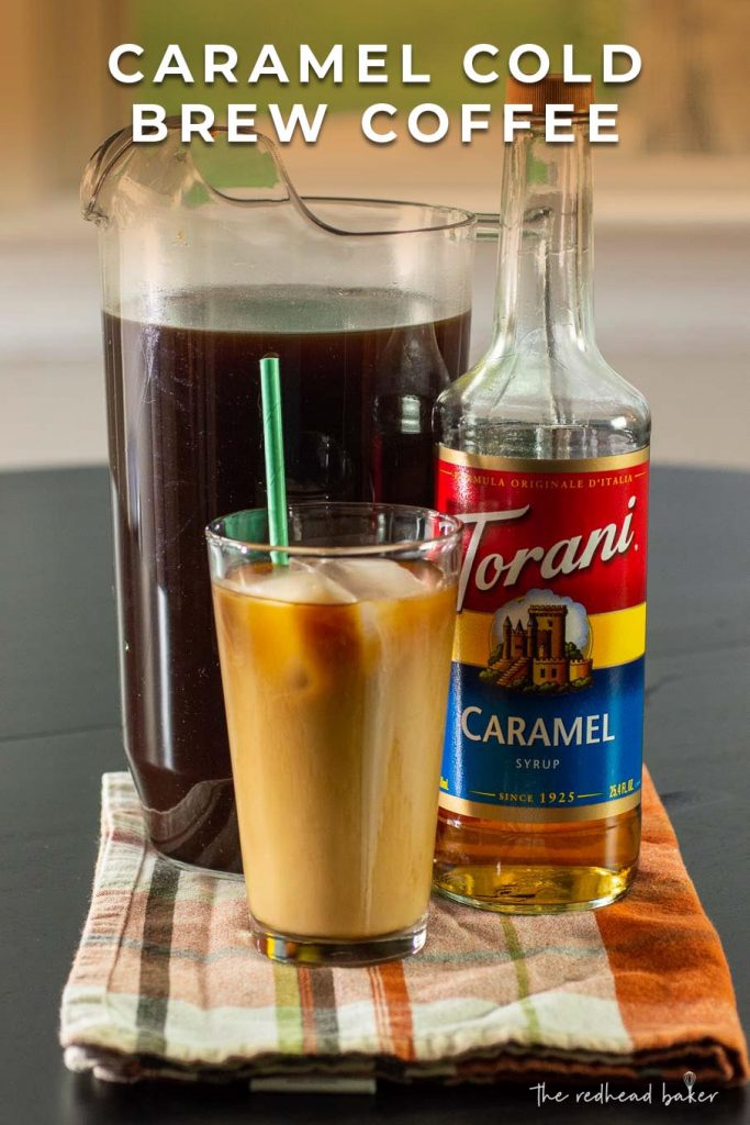 A pitcher of caramel cold brew with a bottle of Torani and a glass of cold brew