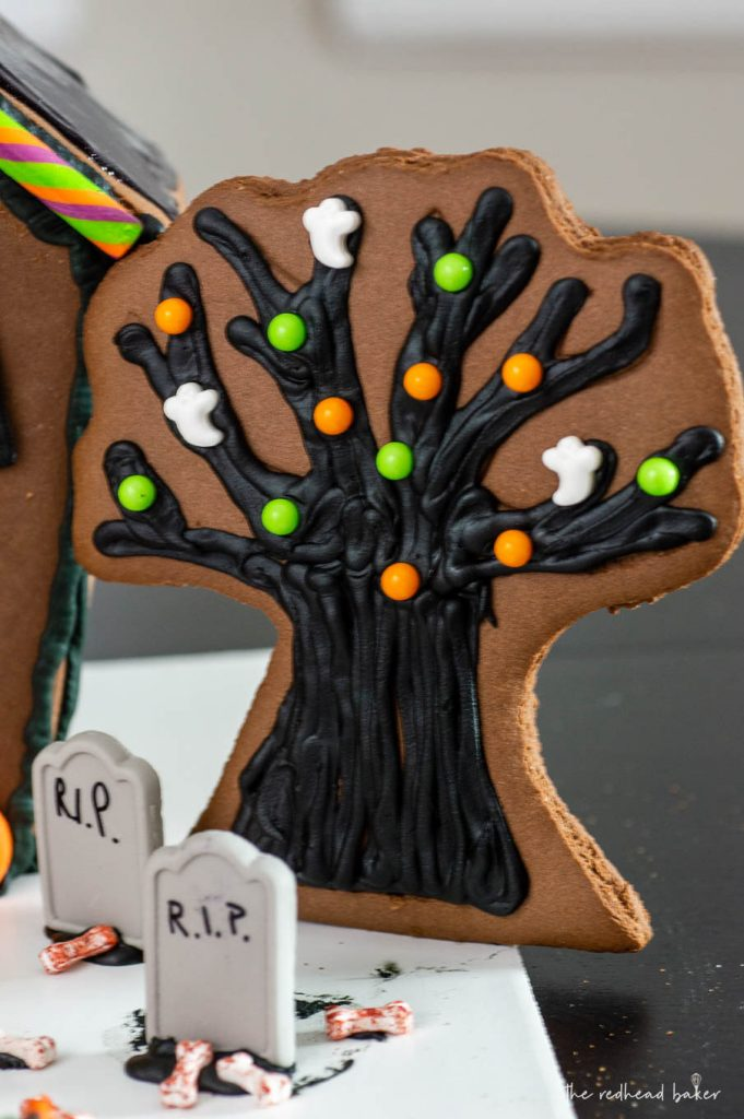 Wilton makes it easy to create a spooky haunted Halloween cookie house with kits, which includes pre-made cookie house pieces, trees, and candy decorations. You can also incorporate other Wilton products! #HalloweenTreatsWeek