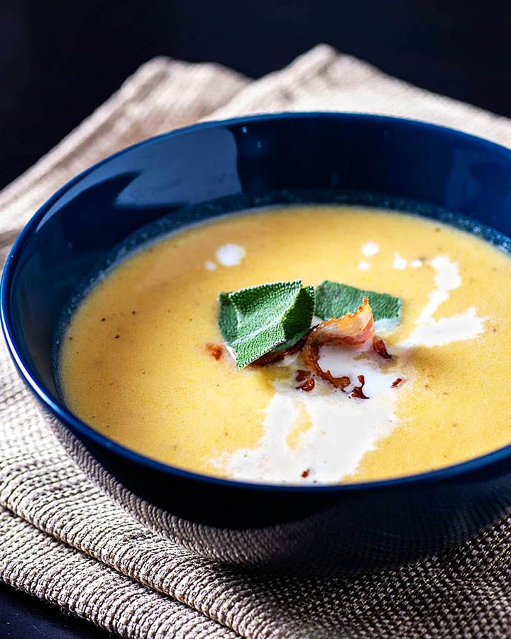 Roasted Butternut Squash Bisque is a smooth and creamy soup flavored with squash, apples, and herbs. A crispy bacon garnish gives contrasting texture.