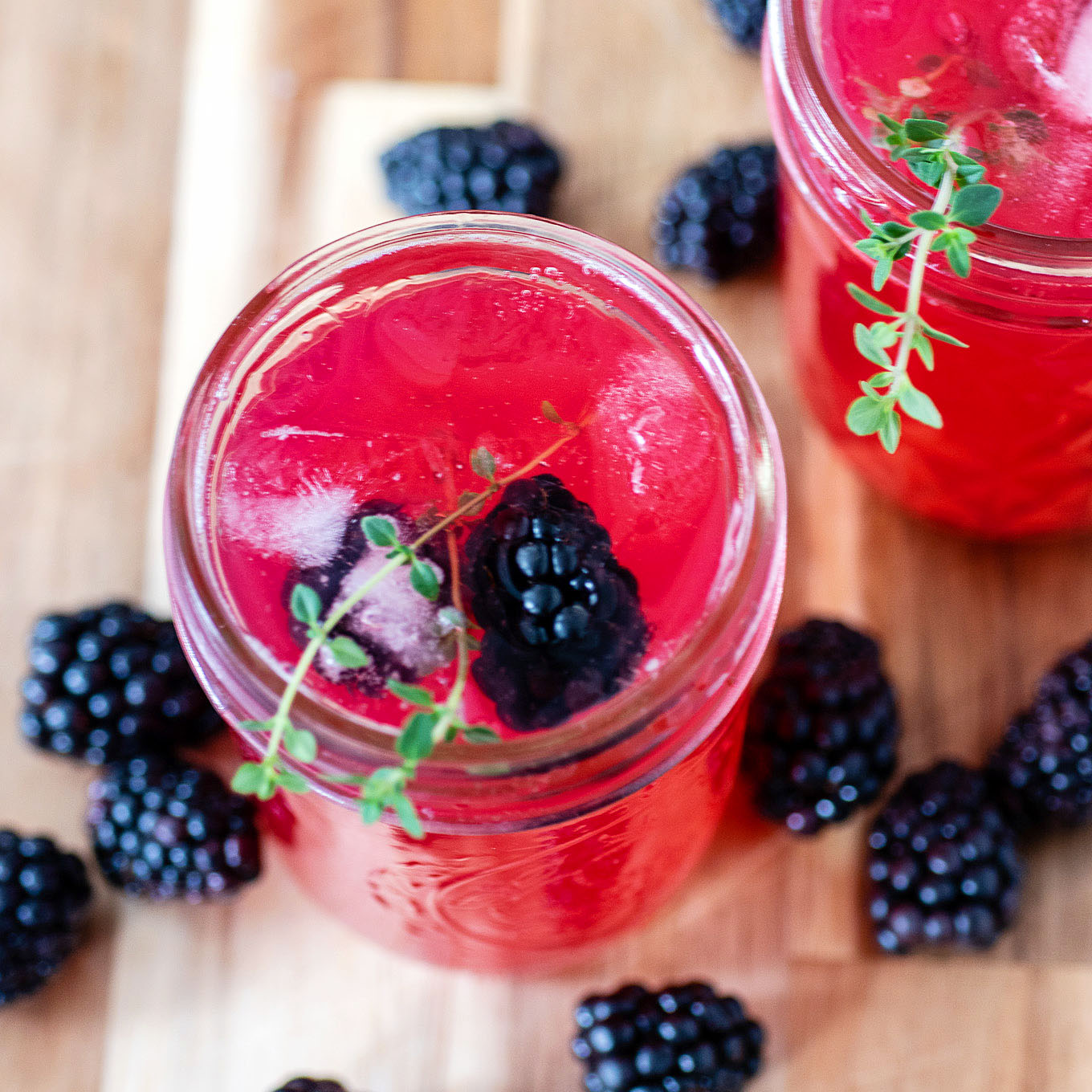An overhead view of a glass of blackberry thyme collins garnished with thyme and fresh blackberries