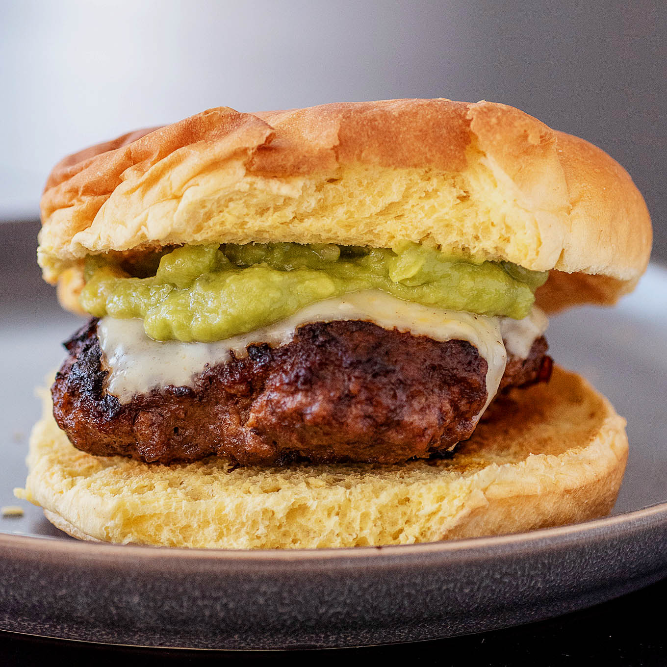 A chipotle guacamole burger on a dark gray plate