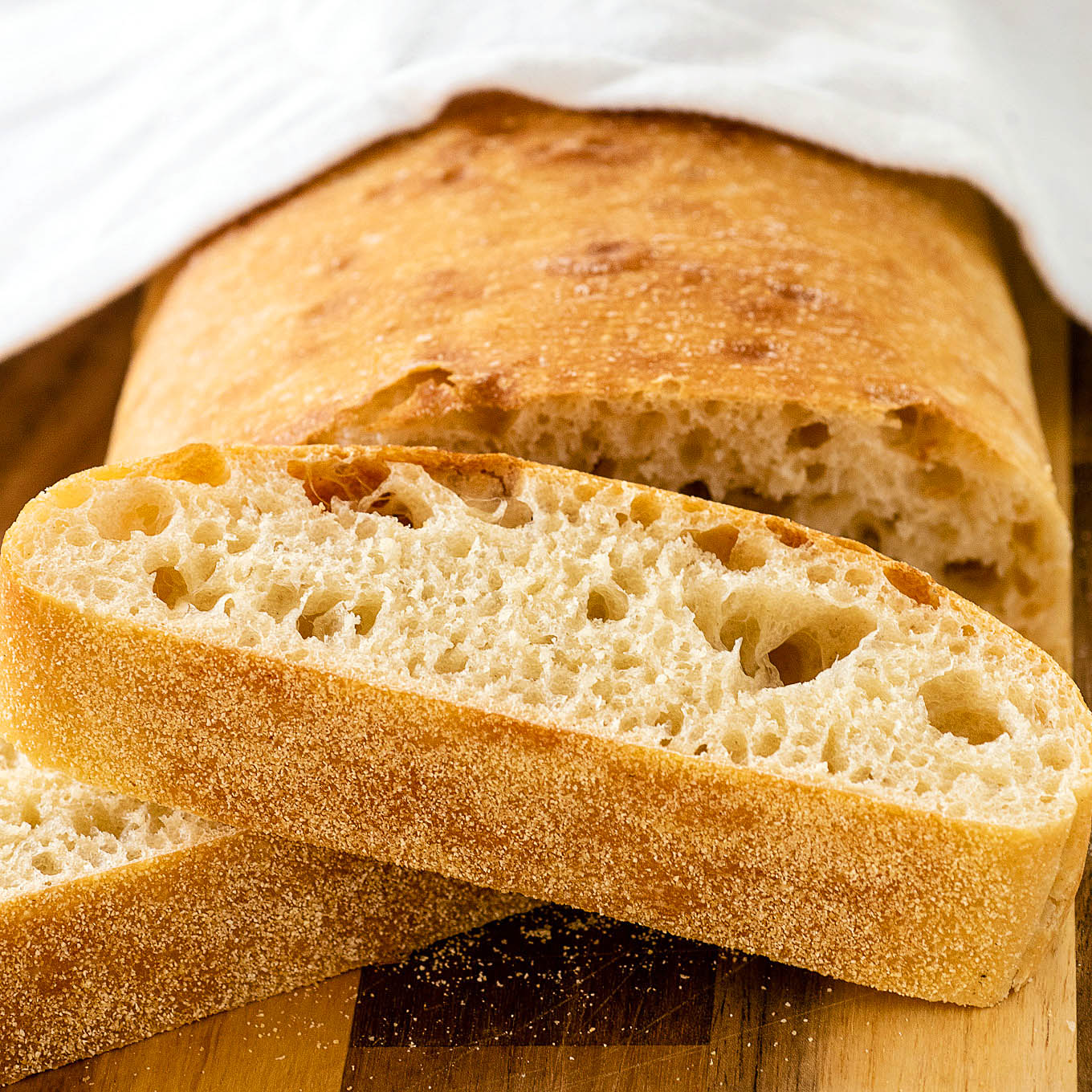 A cut loaf of ciabatta bread with two slices piled in front