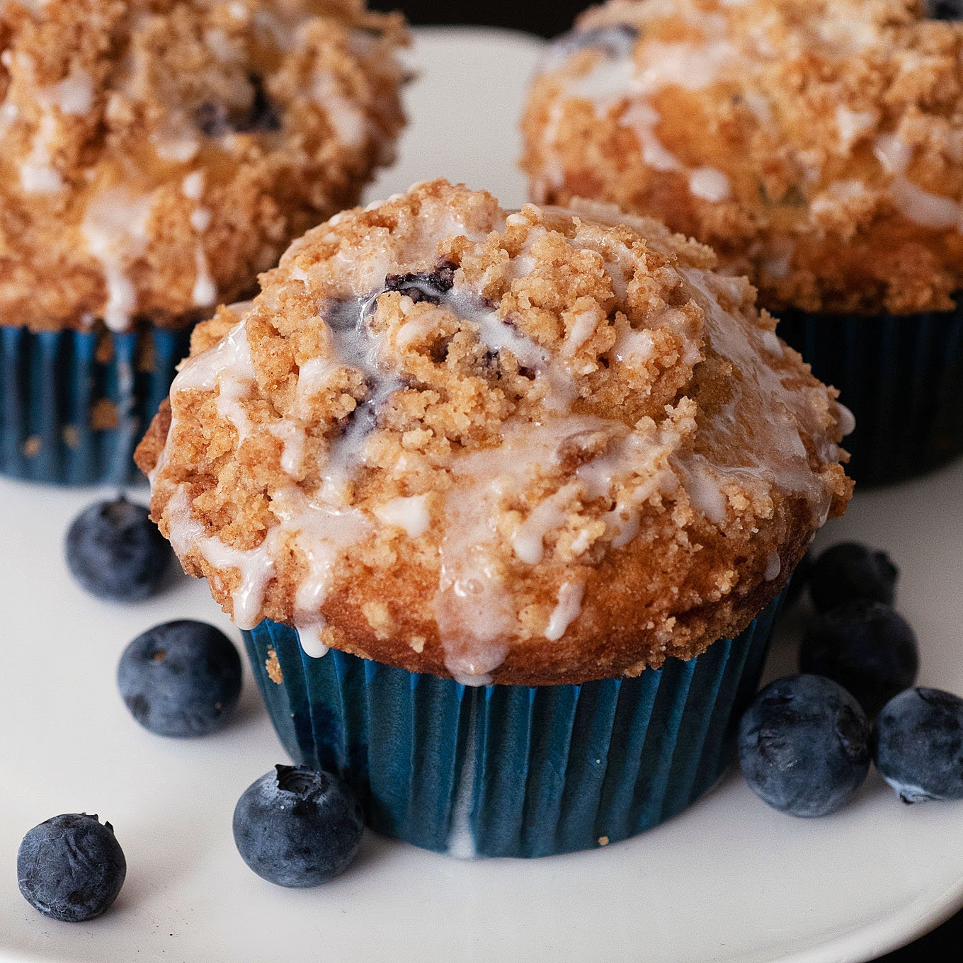 Three blueberry buttermilk muffins on a white serving stand alongside fresh blueberries