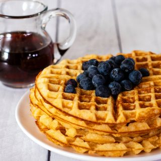 A stack of buttermilk waffles topped with blueberries in front of a jar of maple syrup