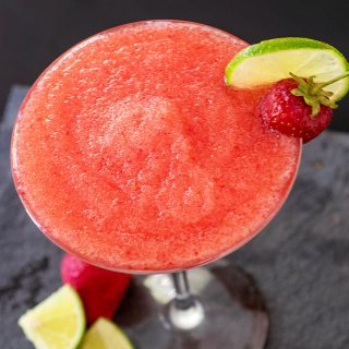 A frozen strawberry daiquiri garnished with a fresh strawberry and a lime slice