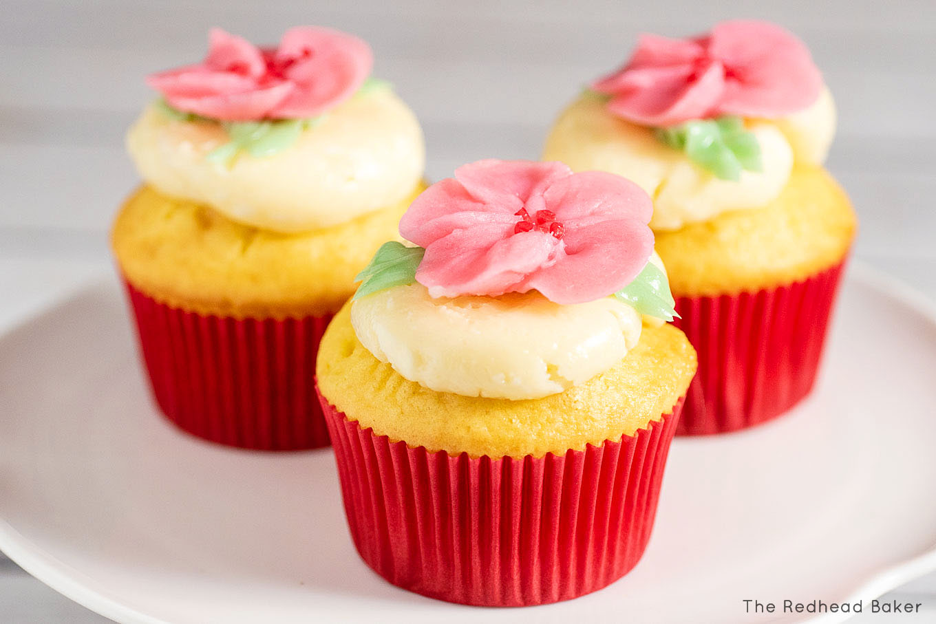 Three cupcakes frosted with swiss buttercream and topped with buttercream cherry blossoms