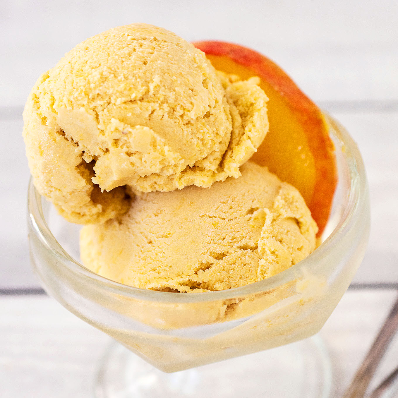 A close-up of two scoops of ice cream in a glass dish with a peach slice