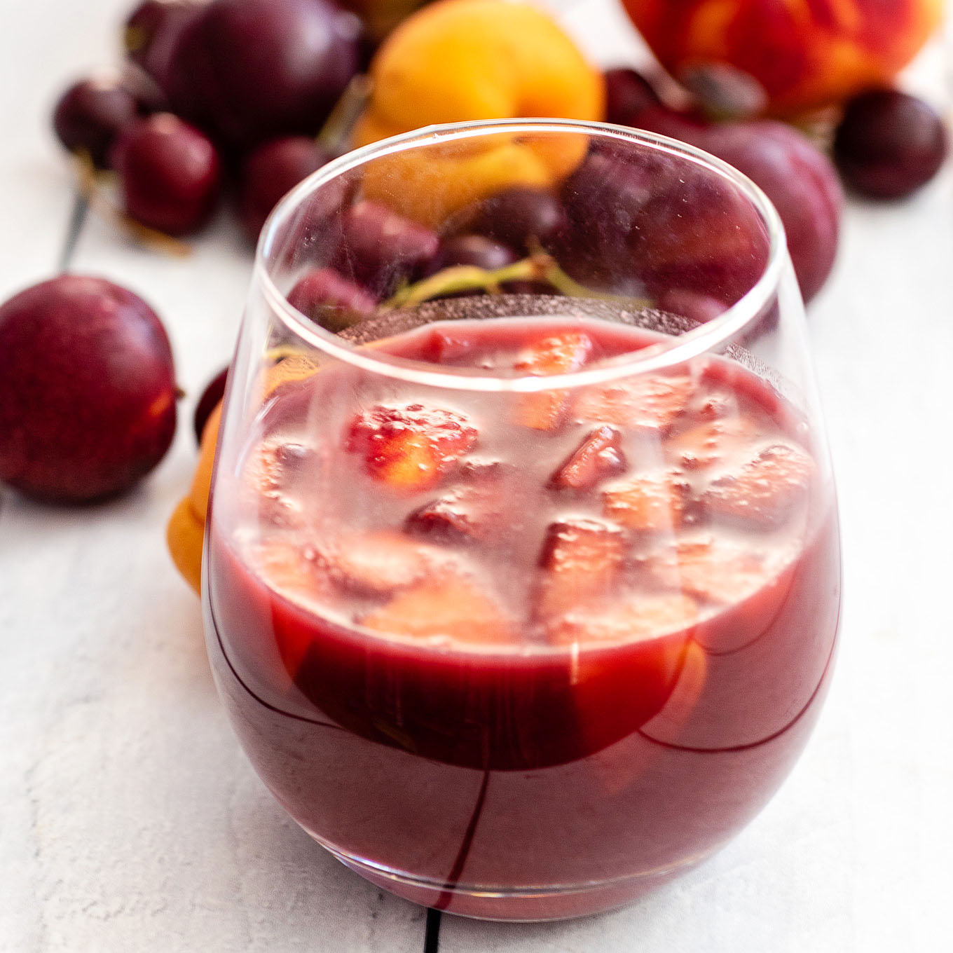 A close-up of a glass of grilled stone-fruit sangria with various stone fruits in the background