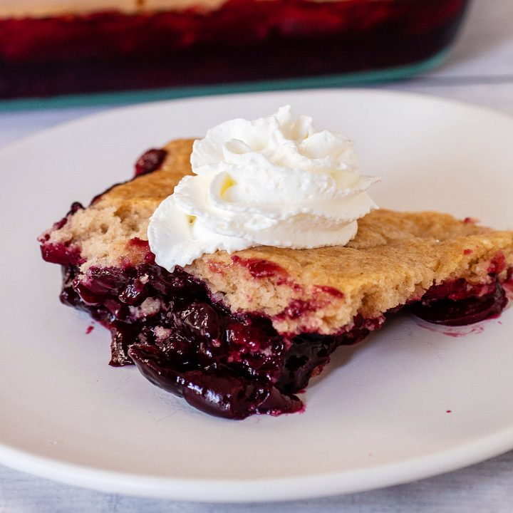 A portion of cherry cobbler topped with whipped cream