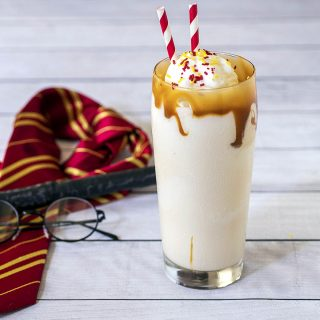 A butterbeer milkshake in front of a Gryffindor tie, a wand and a pair of glasses