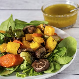 Roasted fall veggie salad on a white plate in front of a dish of cider vinaigrette