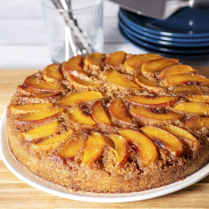 Peach upside down cake on a white serving plate, on top of a wooden cutting board