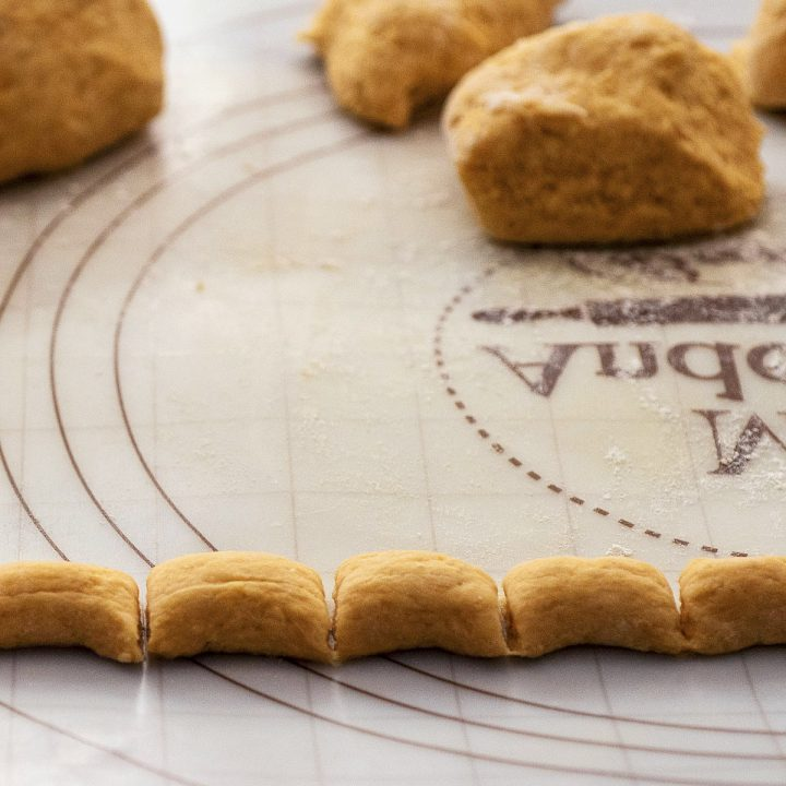 A rope of pumpkin gnocchi dough cut into 1-inch sections