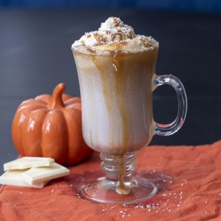 A mug of pumpkin white hot chocolate topped with caramel whipped cream and caramel drizzle