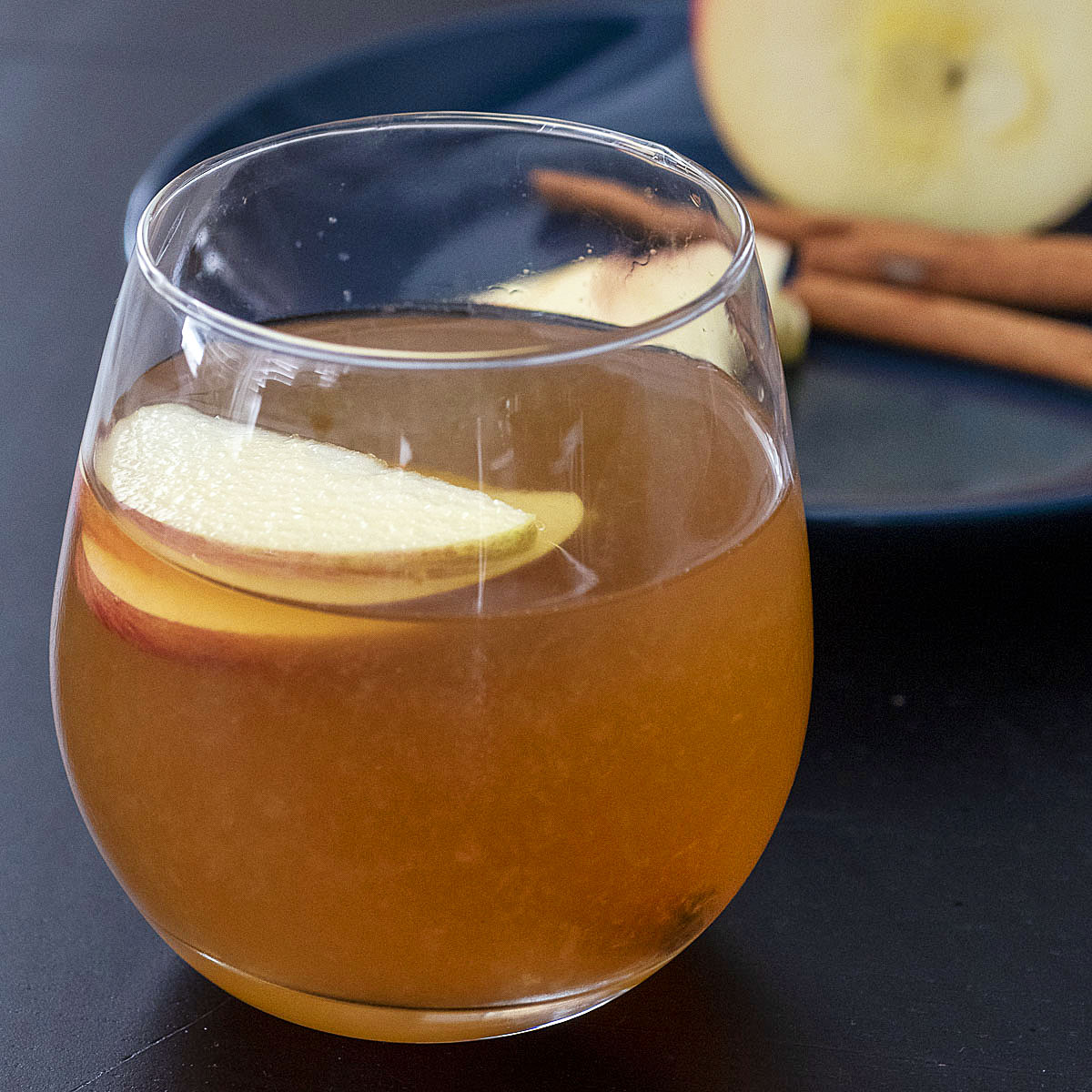 A glass of whiskey sour in front of a blue plate with apple slices, half an apple and cinnamon sticks